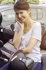 Woman sitting on parked motorcycle  talking on cell phone