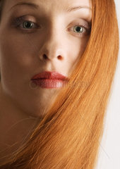 Woman with red hair  wearing lipstick  portrait