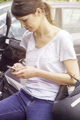 Woman leaning against motorcycle  text messaging with cell phone