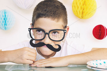 Boy wearing fake glasses and mustache at a birthday party  portrait
