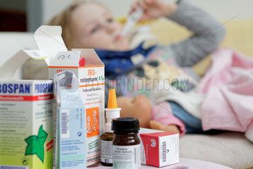 Stuttgart  Deutschland  ein Maedchen liegt krank im Bett und misst Fieber