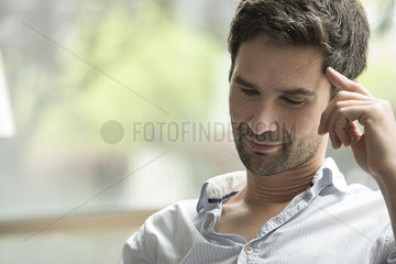 Man looking down attentively with finger pressed against temple