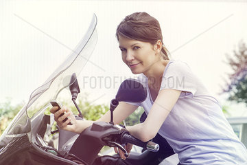 Woman leaning against motorcycle  using smartphone
