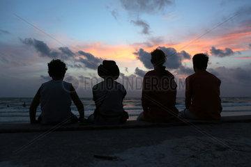 Pass A Grille  Vereinigte Staaten von Amerika  Silhouette  Familie sitzt bei Daemmerung am Strand