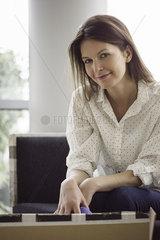 Woman sitting on sofa  smiling  portrait