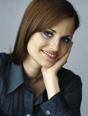 Woman holding head  smiling  portrait