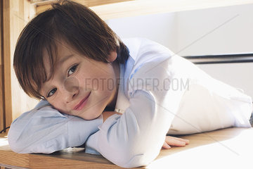 Boy resting head on arms  smiling  portrait