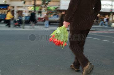 Berlin  Mann mit Tulpenstrauss ueberquert eine Strasse