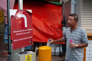 Singapur  Republik Singapur  Mann isst ein Eis in Chinatown