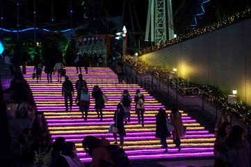 Tokio  Japan  Fussgaenger gehen eine beleuchtete Treppe hoch