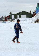 Qeqertarsuaq  Daenemark  Mann vom Volk der Inuit laeuft durch den Schnee