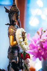 Wassergott Skulptur ist mit thailaendischer Blumengirlande geschmueckt