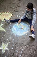 Maedchen malt Erde mit Kreide auf Gehweg