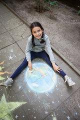 Maedchen malt Erde mit Kreide