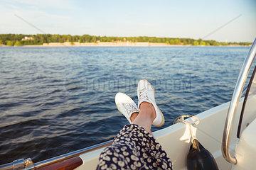 Frau streckt auf Motorboot die Beine aus