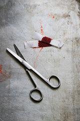Schere und blutiges Pflaster