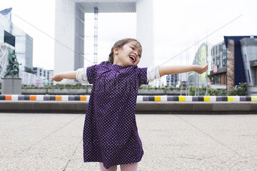 Little girl standing with her head back and arms outstretched in front of the Grande Arche  Paris  France