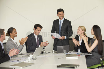 Executive receiving applause from colleagues during presentation