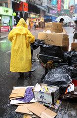Hong Kong  China  Frau sammelt bei Regen alte Kartons ein