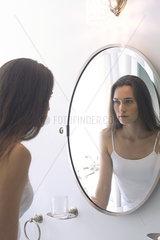 Woman looking at self in bathroom mirror