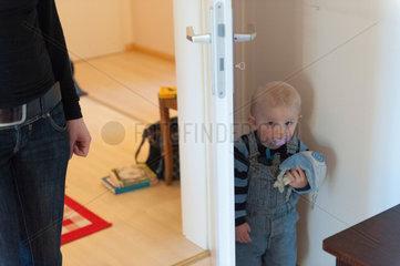 Freiburg  Deutschland  kleines Kind versteckt sich hinter einer Tuer