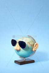 Globus mit Sonnenbrille vor blauem Hintergrund