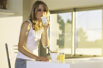 Teenage girl at breakfast table  drinking glass of milk