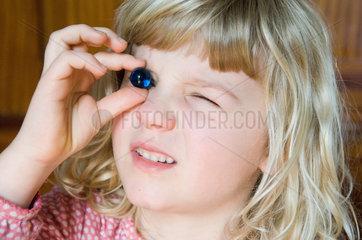 Berlin  Kind schaut durch eine Glaskugel