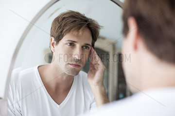 Man looking at self in mirror with concerned look