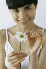 Young woman plucking petals from flower  smiling  portrait