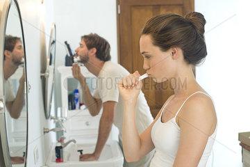 Woman brushing teeth  husband shaving