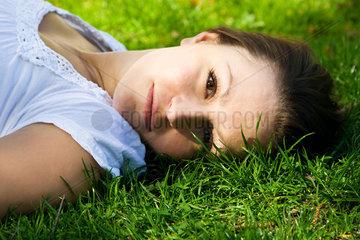 Berlin  Deutschland  junge Frau liegt vertraeumt im Gras