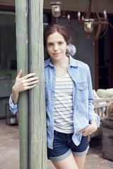 Young woman leaning against wooden post  portrait