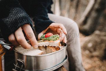 Frau holt vegetarisches Brot aus Brotdose