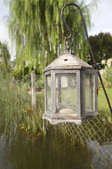 Old-fashioned lantern hanging over lake