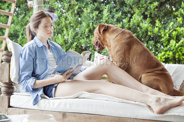 Young woman sitting beside dog outdoors  reading book
