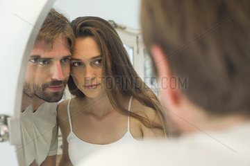 Couple cheek to cheek looking into mirror together
