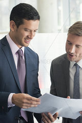 Business associates discussing document together