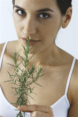 Young woman smelling spring of fresh rosemary  looking at camera