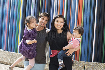 Family holding standing in front of colorful striped sculpture  La Defense  Paris  France