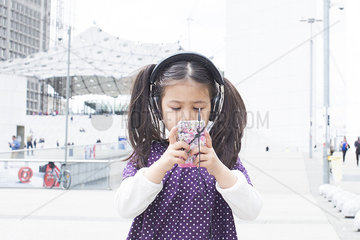 Girl looking at smartphone and listening to headphones outdoors