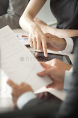 Executives reviewing document in meeting  cropped