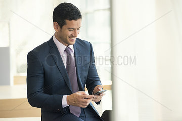 Businessman looking at smartphone and smiling