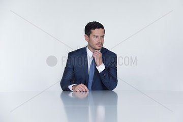 Businessman seated at table  looking away in thought