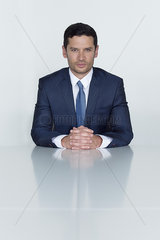 Businessman sitting at conference table with clasped hands  portrait