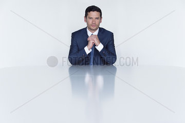 Confident businessman seated at table  portrait