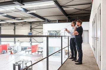 Two men talking on factory shop floor