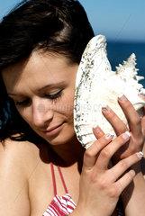 Ahrenshoop  Deutschland  eine junge Frau lauscht dem Meeresrauschen
