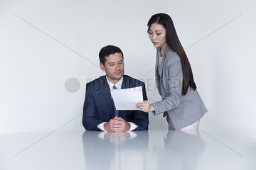 Business associates looking at document in meeting