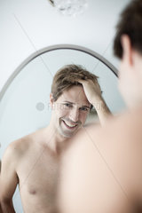 Man with hands in hair looking at self in mirror with look of amusement